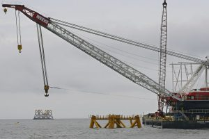 A construction crane works over a foundation installed for a wind turbine by Deepwater Wind off the coast of Block Island, R.I., in July 2015. (AP Photo/Stephan Savoia, File)