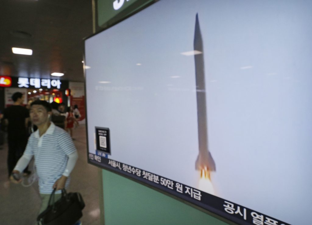 A man passes by a TV news program with file footage of a North Korean rocket launch at the Seoul Railway Station in Seoul, South Korea, Wednesday, Aug. 3, 2016. North Korea fired a ballistic missile into the sea on Wednesday South Korea's military said, the fourth reported weapons launch the North has carried out in about two weeks. (AP Photo/Ahn Young-joon)