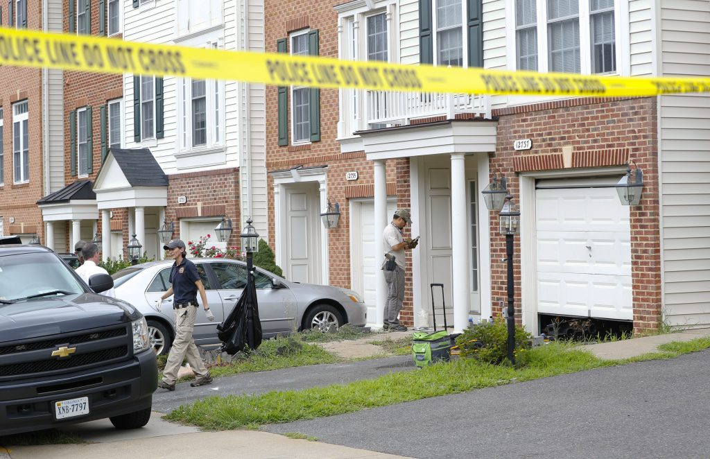 Law enforcement officers are seen outside the home of Nicholas Young, a Washington Metro Transit Officer, Wednesday, Aug. 3, 2016, in Fairfax, Va., Young was arrested at Metro's headquarters in Washington and charged with a single count of attempting to provided material support to a terrorist group. (AP Photo/Pablo Martinez Monsivais)