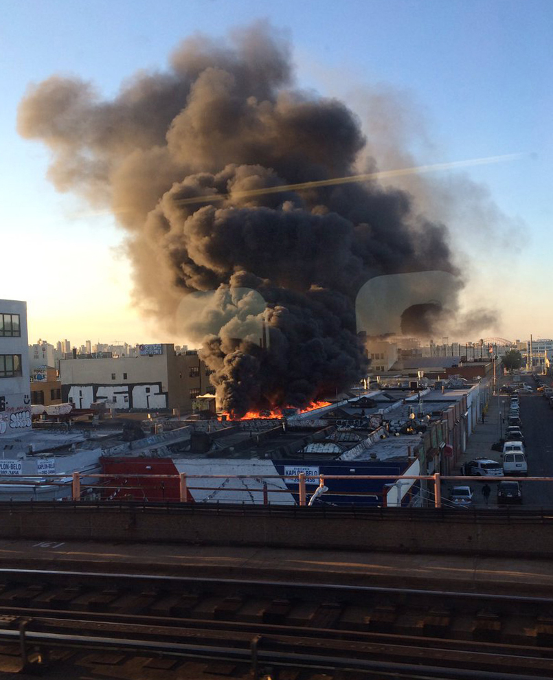 In this photo provided by Reena Karani, MD, MHPE, a warehouse fire rages in the Queens borough of New York, Wednesday, Aug. 3, 2016. Fire officials say over a hundred firefighters and emergency workers responded to 3-alarm blaze. (Reena Karani MD, MHPE via AP)