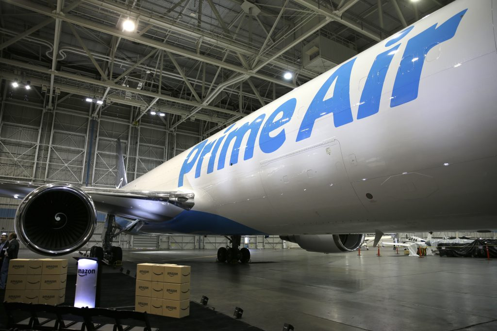 "Amazon.com boxes are shown stacked near a Boeing 767, an Amazon ""Prime Air"" cargo plane on display Thursday, Aug. 4, 2016, in a Boeing hangar in Seattle. Amazon unveiled its first branded cargo plane Thursday, one of 40 jetliners that will make up Amazon's own air transportation network of 40 Boeing jets leased from Atlas Air Worldwide Holdings and Air Transport Services Group Inc., which will operate the air cargo network. (AP Photo/Ted S. Warren)"