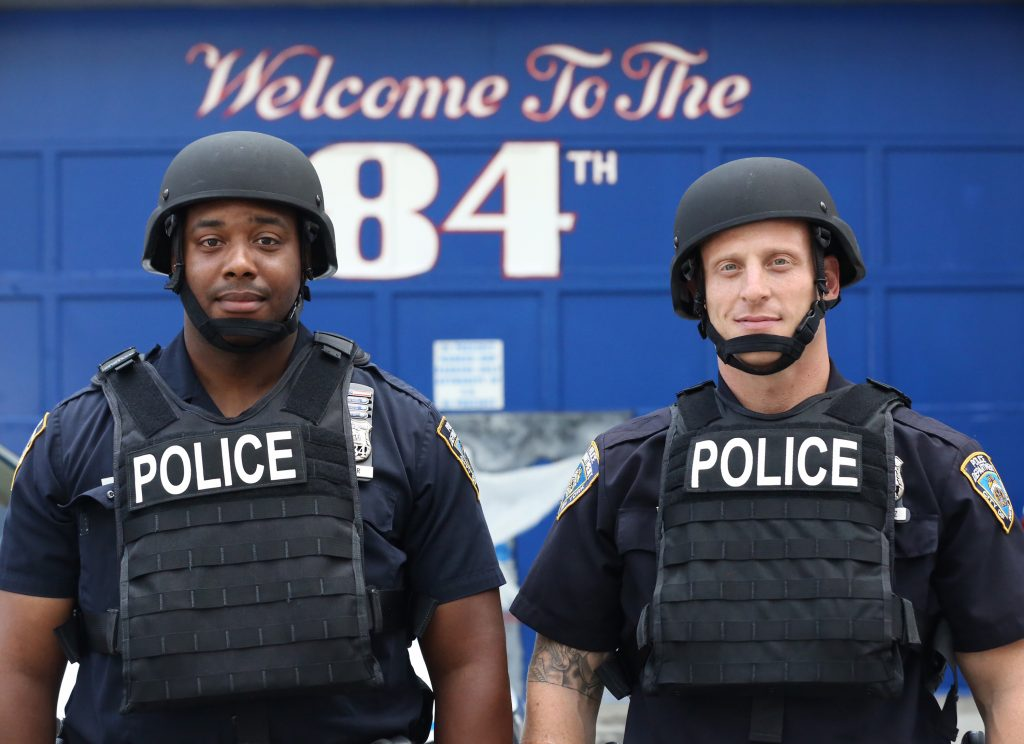 In this July 25, 2016 photo provided by the New York Police Department, Jamal Skinner, left, and Evan Aronowitz, patrol officers with the 84th Precint, model ballistic body armor and helmets during a news conference at the 84th Precinct in the Brooklyn borough of New York. The NYPD plans to distribute 20,000 helmets and 6,000 vests before the end of the year. The equipment will be issued to uniformed patrol officers at a time when the NYPD is also encouraging them to be more approachable to law-abiding citizens. (NYPD via AP)