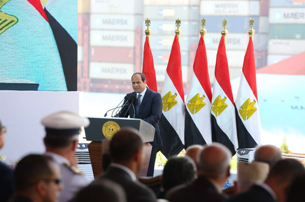 In this photo provided by Egypt's state news agency MENA, Egyptian President Abdel-Fattah el-Sissi, gives a speech marking the first anniversary the first anniversary of the inauguration of an expansion of the Suez Canal, in Suez, Egypt. (MENA via AP)