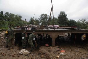 Mexican soldiers remove debris from the remains of a house flattend by a mudslide in Xaltepec on Sunday. (AP Photo/Pablo Spencer)