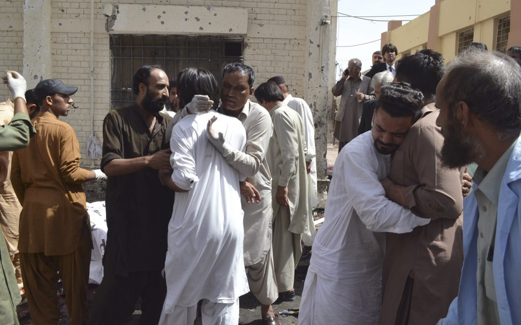People comfort each other following a bomb blast in Quetta, Pakistan, Monday, Aug. 8, 2016. A powerful bomb went off on the grounds of a government-run hospital Monday, killing dozens of people, police said. (AP Photo/Arshad Butt)