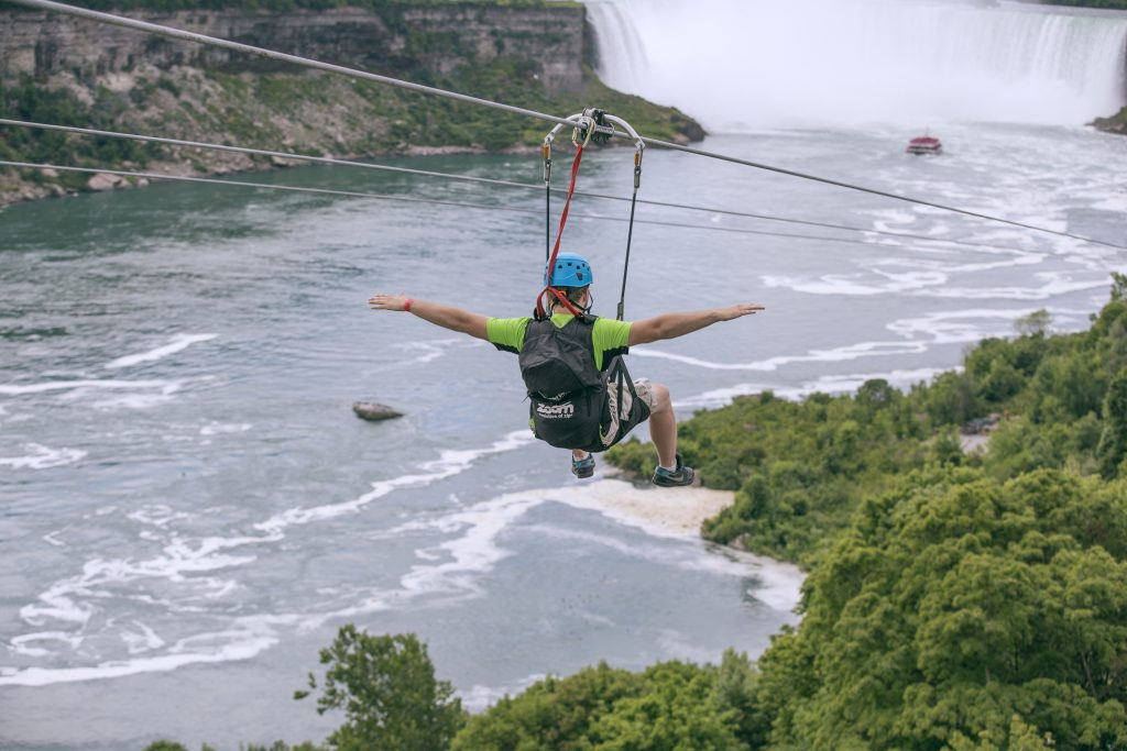 A tourist suspended above the water from zip lines makes his way at speeds of up to 40 mph toward the the mist of the Horseshoe Falls, on the Ontario side of Niagara Falls. (Kien Tran/WildPlay Ltd. via AP)