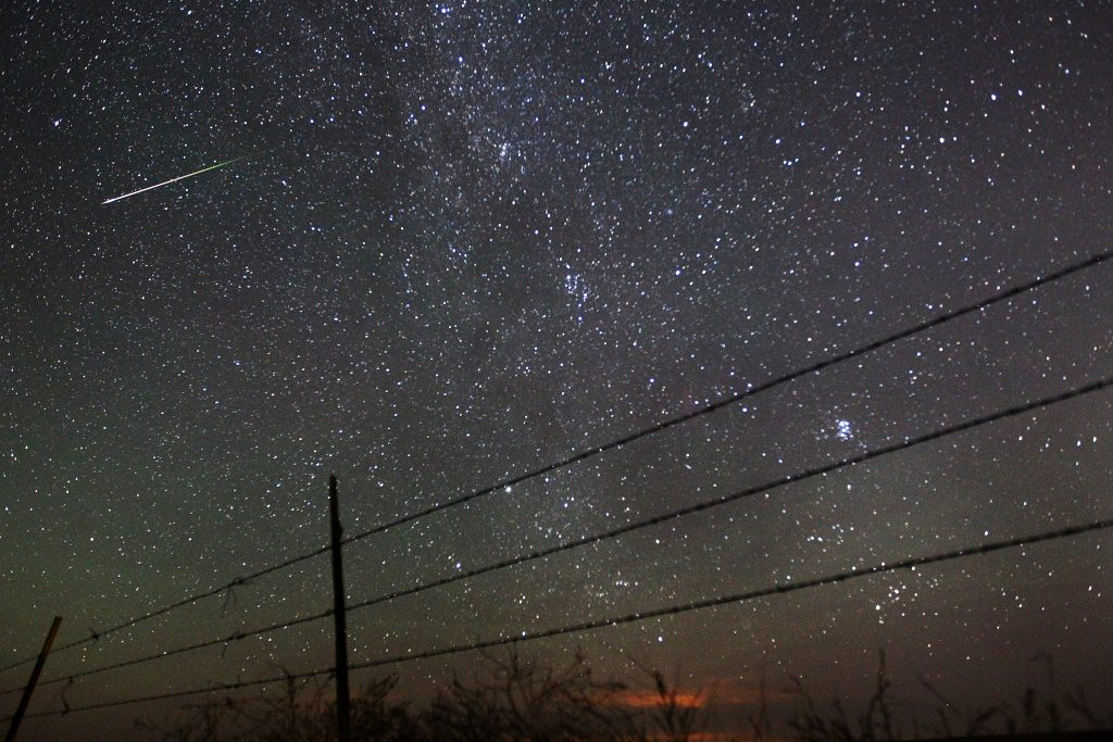 FILE - In this early morning, Aug. 13, 2013 file photo, a meteor streaks past the faint band of the Milky Way galaxy above the Wyoming countryside north of Cheyenne, Wyo., during a Perseids meteor shower. (AP Photo/The Wyoming Tribune Eagle, Blaine McCartney)