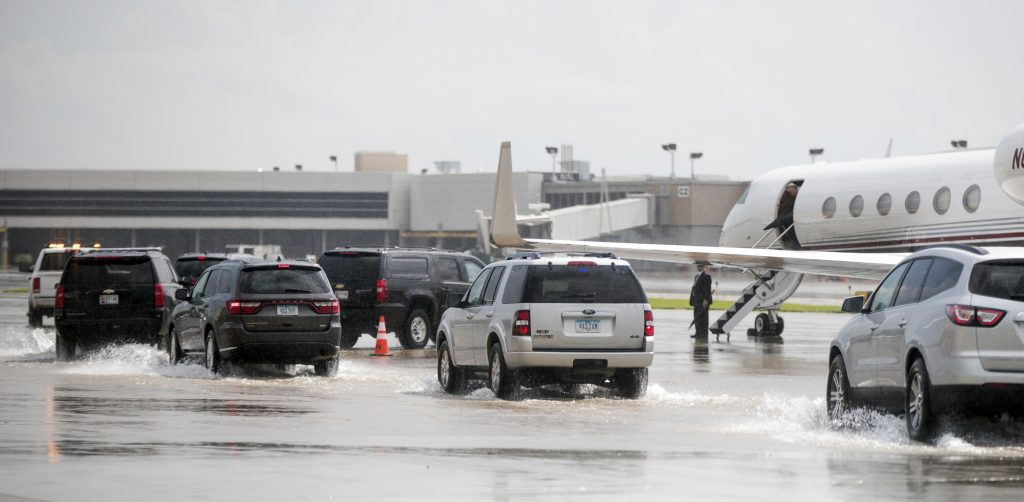 The motorcade carrying Democratic presidential candidate Hillary Clinton arrives at her plane moments after a severe downpour at Des Moines International Airport in Des Moines, Iowa, Wednesday, Aug. 10, 2016, as Clinton travels to Detroit Metropolitan Wayne County Airport. (AP Photo/Andrew Harnik)