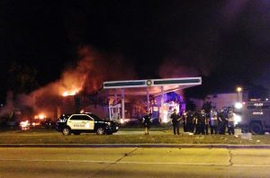Authorities respond near a burning gas station as dozens of people protest following the fatal shooting of a man in Milwaukee on Saturday. (AP Photo/Gretchen Ehlke)