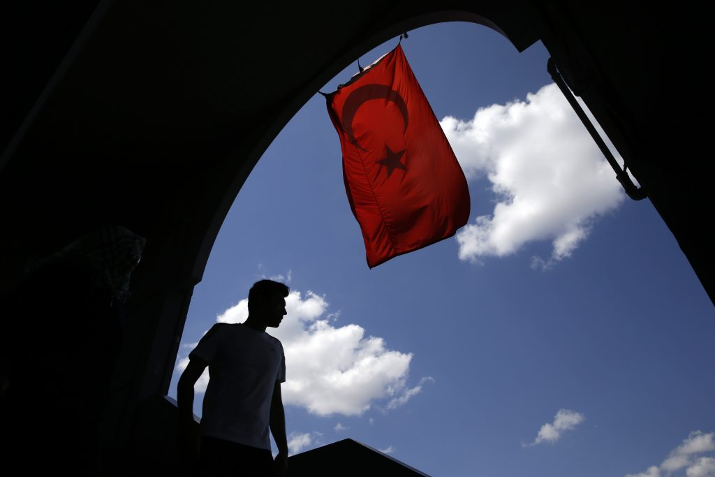 A pedestrian passes under a Turkish flag in Istanbul, Sunday, Aug. 14, 2016. Turkish authorities have prepared an official request for the temporary arrest of United States-based Islamic cleric Fethullah Gulen over his alleged involvement in the coup attempt on July 15, Turkey's state-run Anadolu news agency said Saturday. (AP Photo/Thanassis Stavrakis)