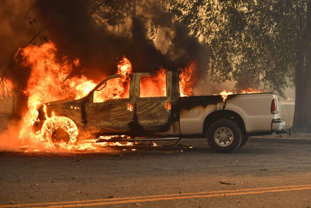 A truck burns on Main Street in the town of Lower Lake, Calif. on Sunday, August 14, 2016. Flames continue to burn out of control in the area. Cal Fire spokeswoman Suzie Blankenship said the fire was creating its own weather pattern and shifted direction Sunday afternoon into populated areas. (AP Photo/Josh Edelson)