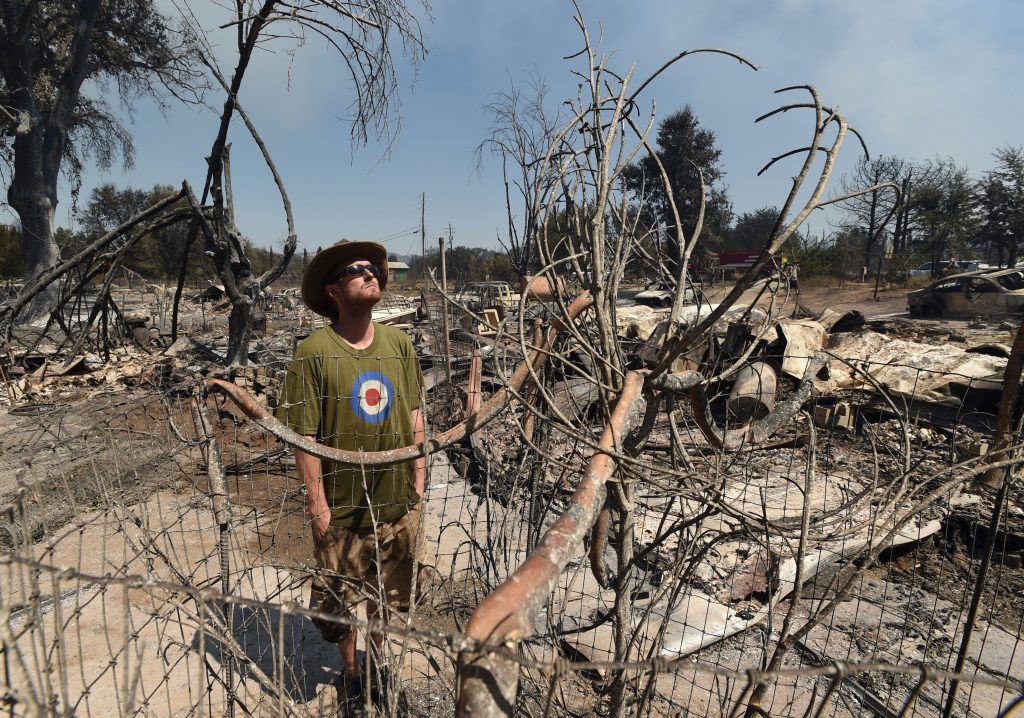 James McCauley looks over the burned-out remains of his residence in the town of Lower Lake, Calif. (AP Photo/Josh Edelson)