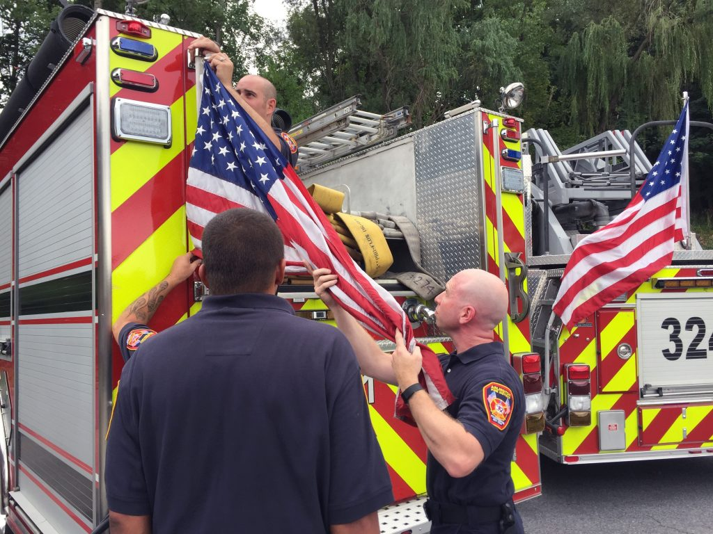 Firefighters remove American flags from a fire truck in Poughkeepsie, N.Y., on Tuesday. (Nina Schutzman/Poughkeepsie Journal via AP)