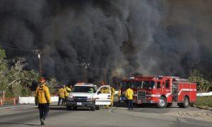 Smoke envelops Highway 138 at Hess Rd in Phelan, Calif., as firefighters prepare to battle a wildfire spreading through San Bernardino County. (AP Photo/Rick McClure)2