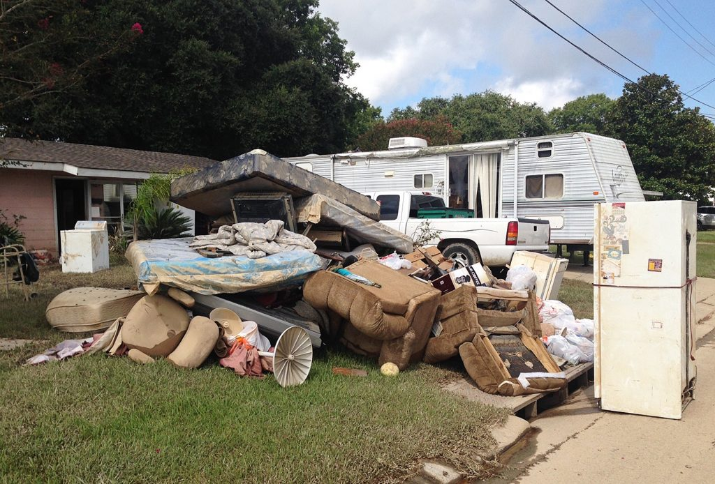 A growing pile of debris sits outside the flood-ravaged home of Carolyn and James Smith in Denham Springs, La., on Wednesday. Smith says she and four other adults will live for the time being in the travel trailer that one of her sons towed to the driveway after weekend flooding inundated the area. (AP Photo/Kevin McGill)
