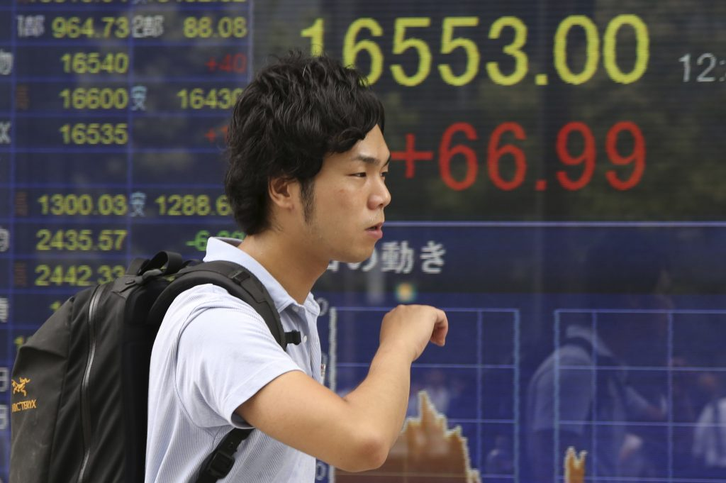 A man walks by an electronic stock board of a securities firm in Tokyo, Friday, Aug. 19, 2016 . Most Asian stock benchmarks drifted lower Friday as investors hunkered down to mull resurgent oil prices and corporate earnings while awaiting a key speech by the Fed chief next week. (AP Photo/Koji Sasahara)