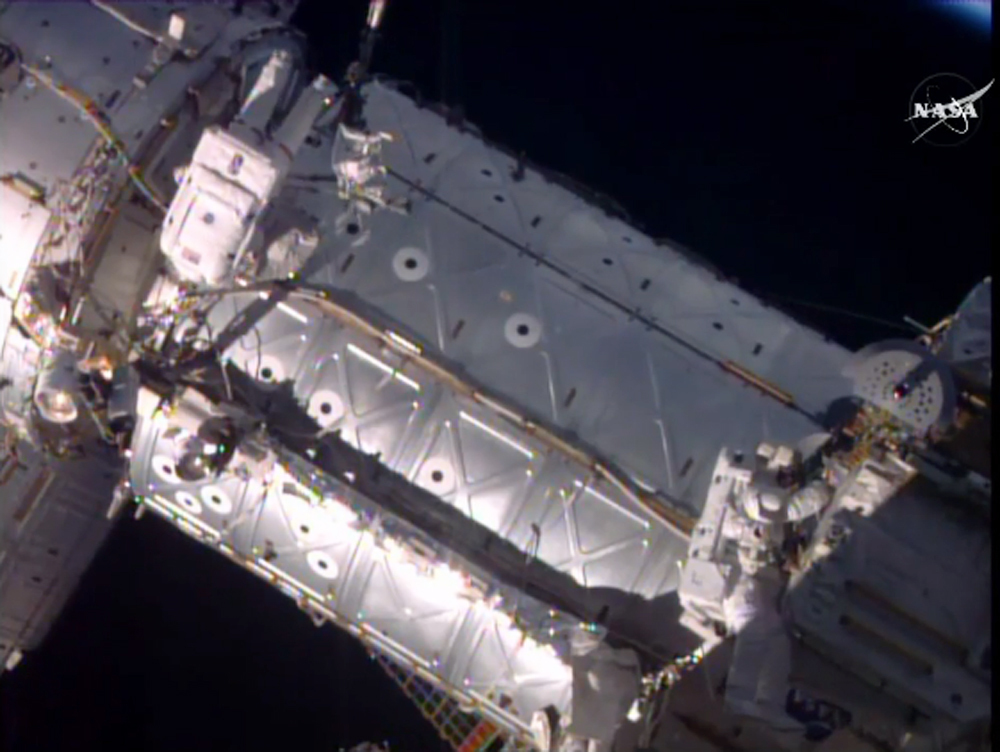 Astronauts taking a spacewalk to hook up a docking port outside the International Space Station on Friday. (NASA via AP)