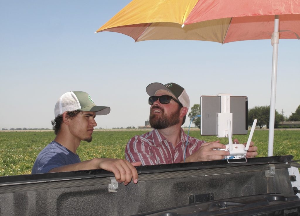Danny Royer pilots a drone over a tomato field near Los Banos, Calif. At left is Christian Cambrelen, a college intern. (AP Photo/Scott Smith)
