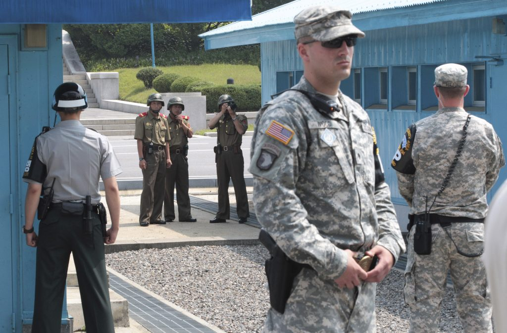 FILE - In this July 27, 2014 file photo, North Korean army soldiers watch the south side while a South Korean and United States Army soldiers stand guard at the border villages of Panmunjom in Paju, South Korea. (AP Photo/Ahn Young-joon, File)
