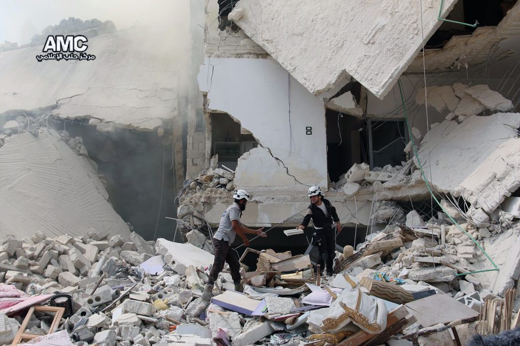 Syrian civil defense workers inspecting damaged buildings after barrel bombs were dropped on the Bab al-Nairab neighborhood in Aleppo, Syria, on Saturday. (Aleppo Media Center via AP)