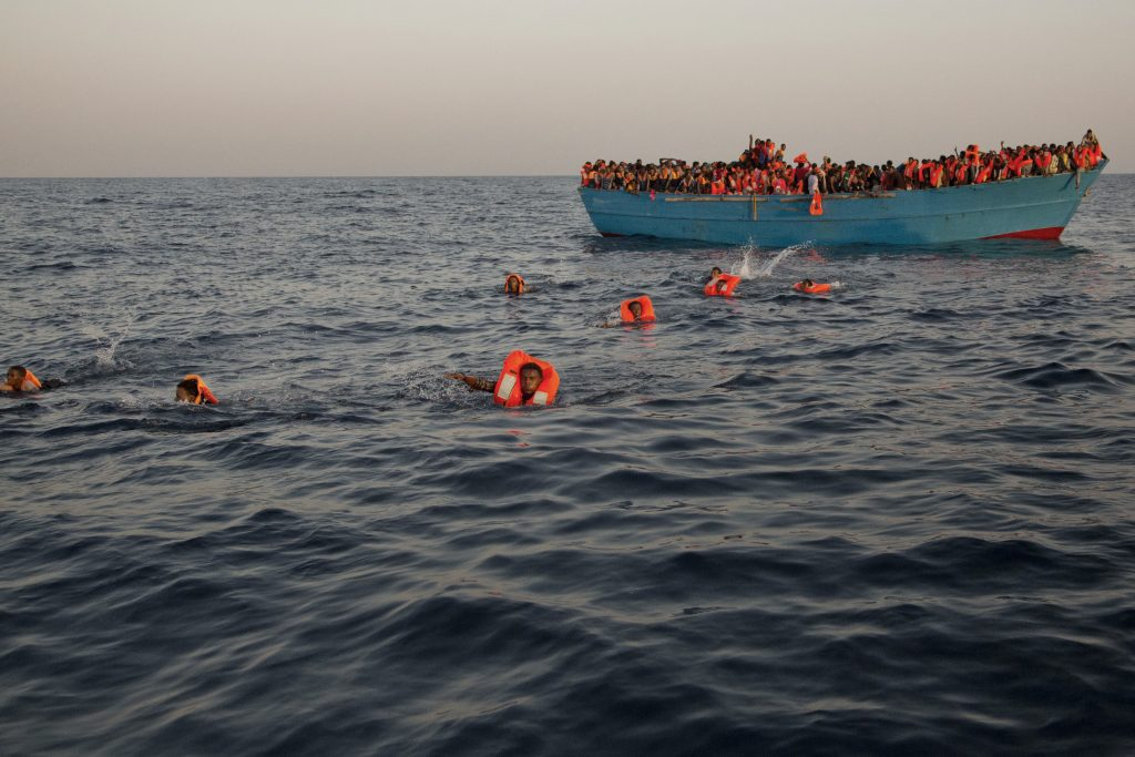 Migrants, most of them from Eritrea, jump into the water from a crowded wooden boat as they are helped by members of an NGO during a rescue operation on the Mediterranean sea, about 13 miles north of Sabratha, Libya, on Monday. (AP Photo/Emilio Morenatti)