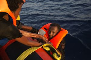 A migrant from Eritrea is helped after jumping into the water from a crowded wooden boat. (AP Photo/Emilio Morenatti)
