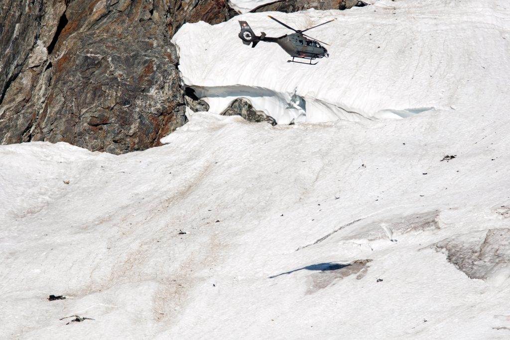 A military helicopter flies above the Chelengletscher glacier in Goeschenen, Switzerland, Wednesday, Aug. 31, 2016. Swiss authorities say the body of a Swiss fighter jet pilot has been found after his U.S.-built F/A-18C aircraft went missing in the Alps two days ago. (Philipp Schmidli/Keystone via AP)