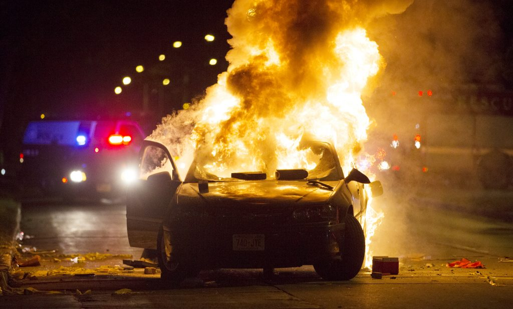 A car burns as a crowd of more than 100 people gathers following the fatal shooting of a man in Milwaukee on Saturday. (Calvin Mattheis/Milwaukee Journal-Sentinel via AP)