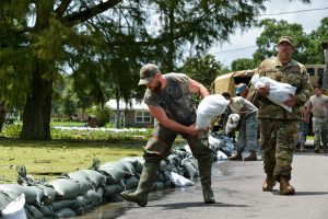 Lake Arthur, La., residents receive help from the Army National Guard to build a sand-bag wall to keep flood waters from the city, on Wednesday. (Scott Clause/The Daily Advertiser via AP)