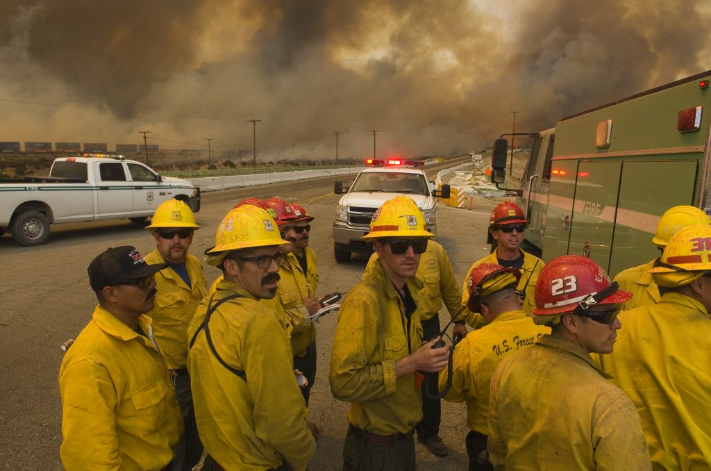 A U.S. Forest Service Hand crew looks for routes to aid in battling a wildfire near Highway 138 and Interstate 15 near Cajon Pass on Tuesday. (James Quigg/The Daily Press via AP)