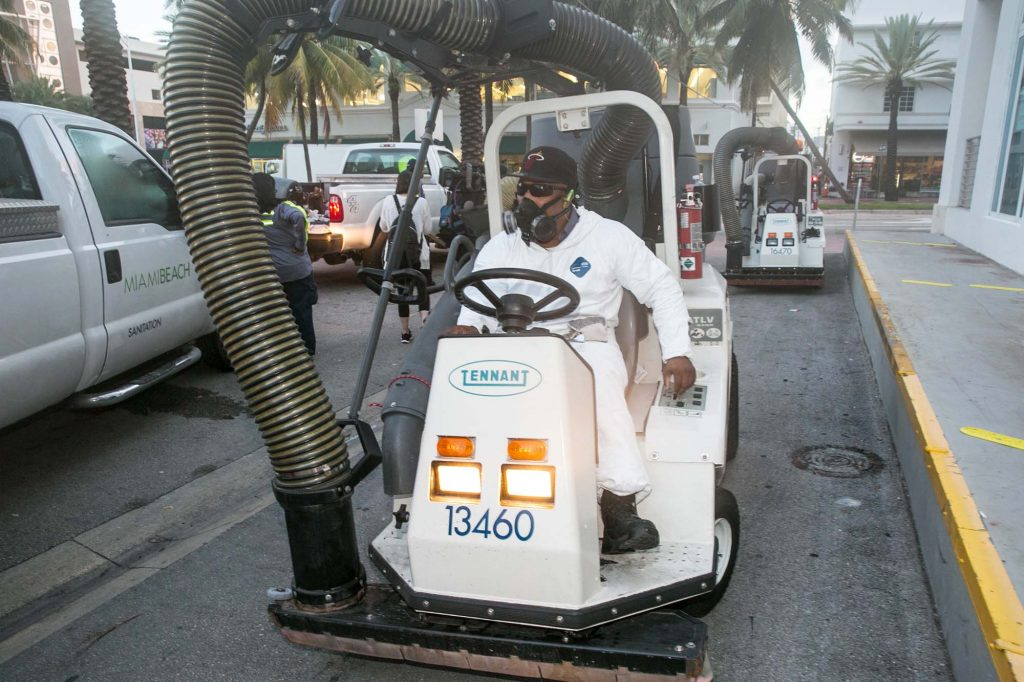 A City of Miami Beach Sanitation worker gets ready to clean the alleyways of South Beach, sucking up still waters and debris with a mobile vacuum, Miami Beach, Fla., as part of the city's Zika clean-up. (C.M. Guerrero/El Nuevo Herald via AP)