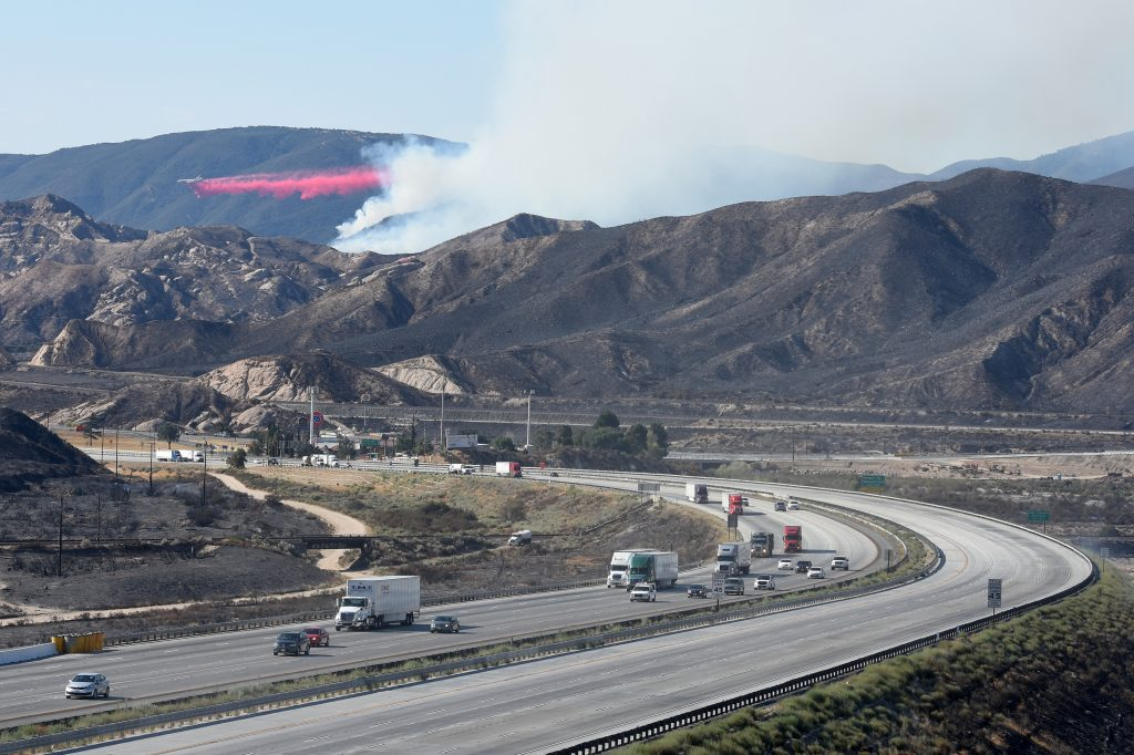 A DC-10 drops fire retardant on a wildfire as southbound Interstate 15 remained closed in the Cajon Pass, Calif., on Thursday. (David Pardo/The Daily Press via AP)