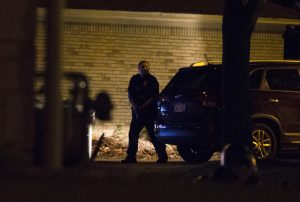A police officer hides behind a car during protests Saturday night.(Calvin Mattheis/Milwaukee Journal-Sentinel via AP)