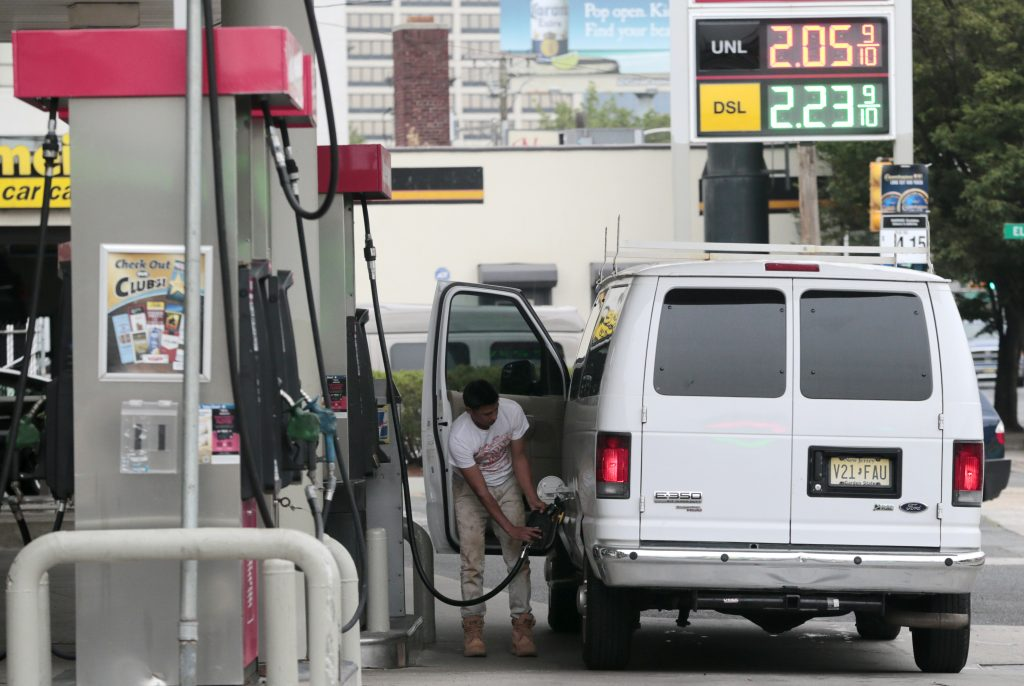 A motorist finishes pumping gas into a van at a gas station in downtown Newark, N.J. (AP Photo/Julio Cortez)