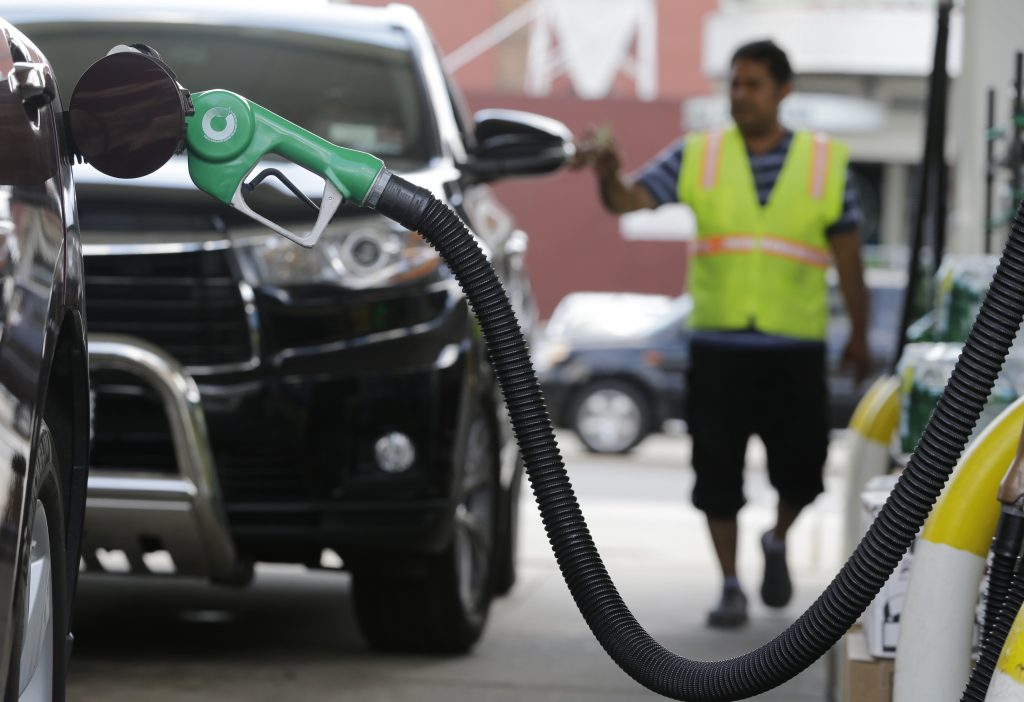 A nozzle pumps gas into a vehicle as Tofail Ahmed collects payment after pumping gas for a motorist at a BP gas station, Thursday, June 30, in Hoboken, N.J. (AP Photo/Julio Cortez)