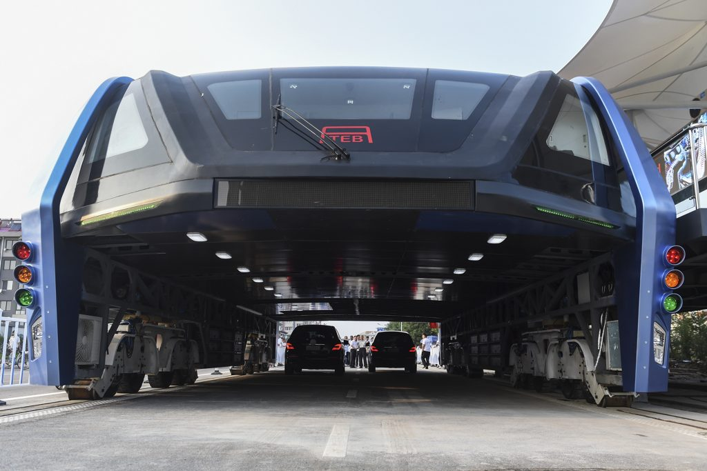 In this Tuesday, Aug. 2, 2016 photo released by Xinhua News Agency, people look at the Transit Elevated Bus TEB-1 run past vehicles as they conducted a test run in Qinhuangdao, north China's Hebei Province. (Luo Xiaoguang/Xinhua via AP)