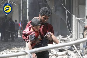 A man carries an injured boy in Aleppo in May. (Civil Defense Directorate in Liberated Province of Aleppo via AP, File)