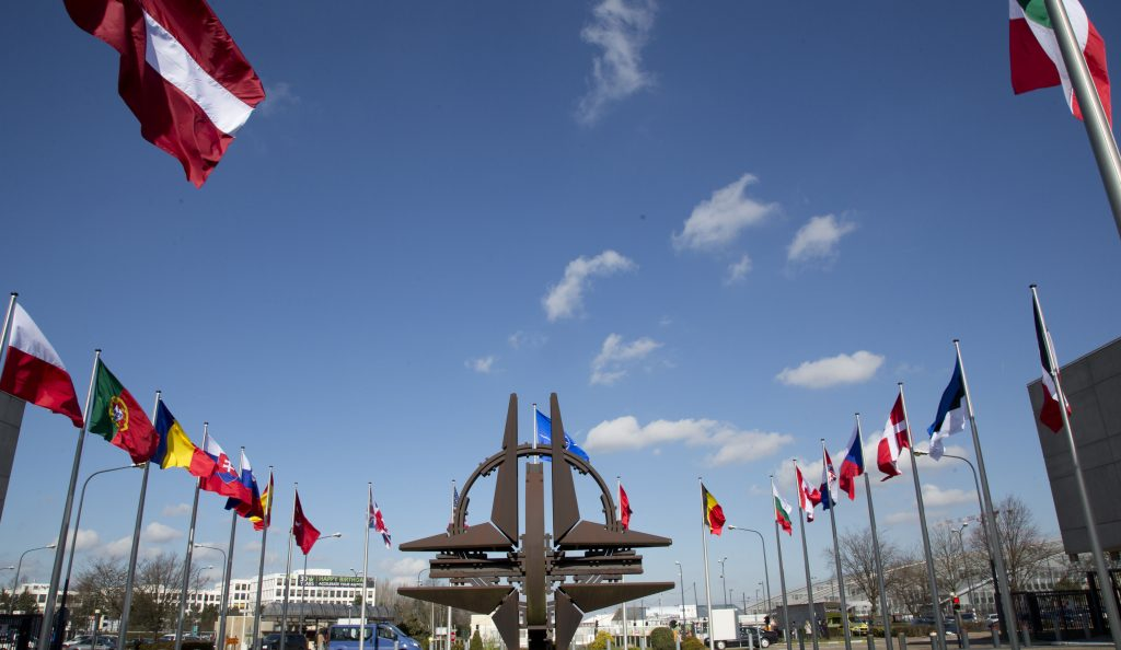 The NATO symbol and flags of the NATO nations outside NATO headquarters in Brussels in this March 2, 2014 photo. (AP Photo/Virginia Mayo)