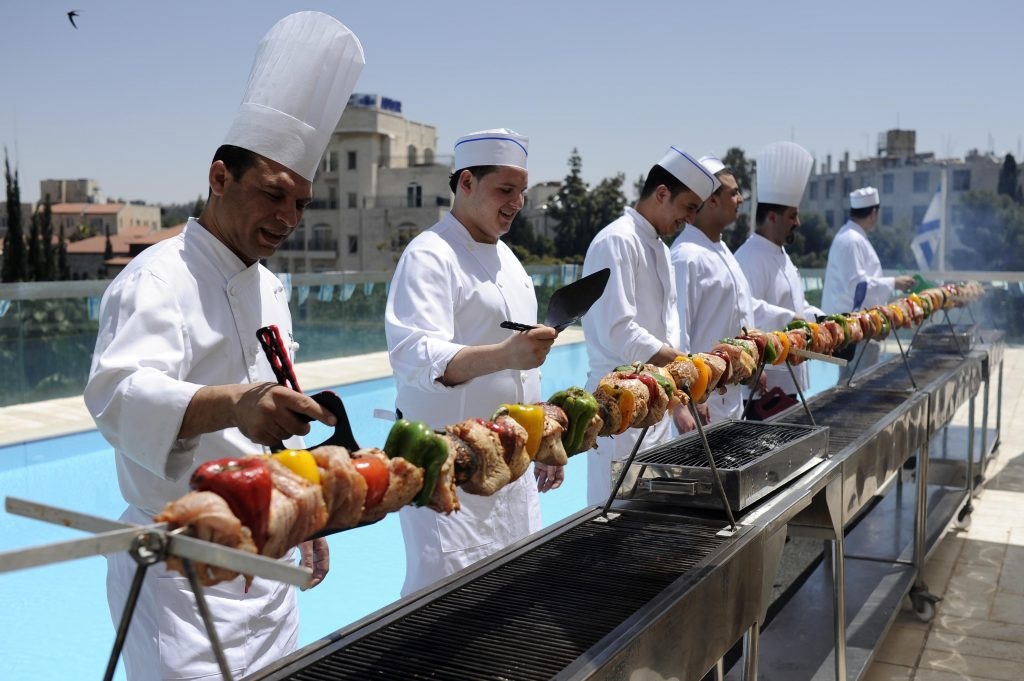 Chefs at a 24-feet-long BBQ grill at the Grand Court Hotel in Yerushalayim cook 70.7 pounds of meat. (Yoav Ari Dudkevitch/Flash90)