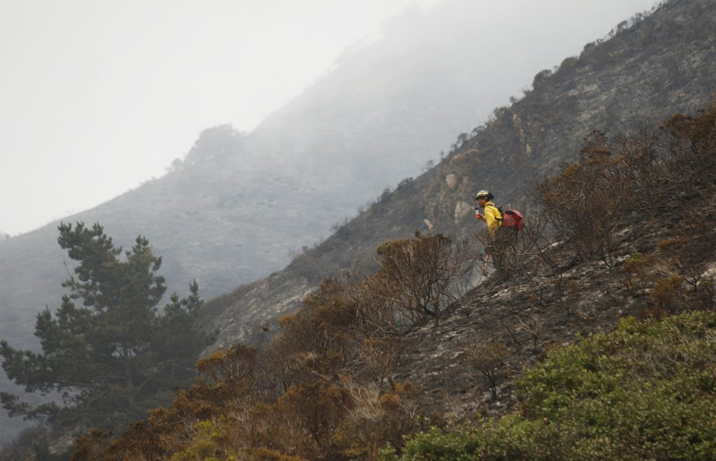 A firefighter stands on steep terrain while fire crews create fire breaks at Garrapata State Park during the Soberanes Fire north of Big Sur, California, U.S. July 31, 2016. REUTERS/Michael Fiala