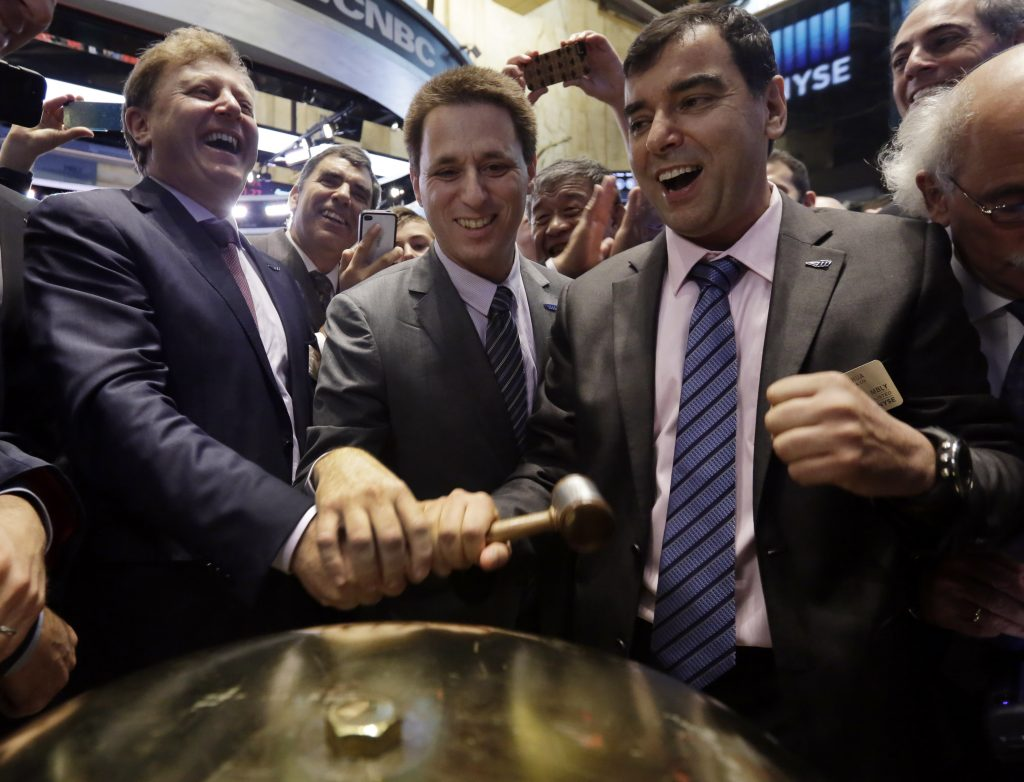 In this Aug. 1, 2014, photo, Mobileye President & CEO Ziv Aviramon, left, CFO Ofer Maharshak, center, and Chairman Amnon Shashua clasp hands to ring a ceremonial bell at their company's IPO, on the floor of the New York Stock Exchange. (AP Photo/Richard Drew, File)