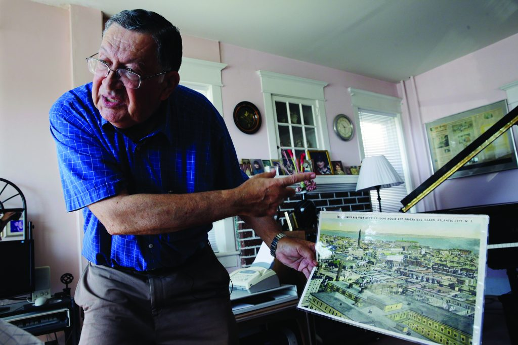 Piano tuner Charlie Birnbaum of Hammonton, NJ, stands in the three-story house where he was raised and displays an old image of places he remembers. (AP Photo/Mel Evans, File)