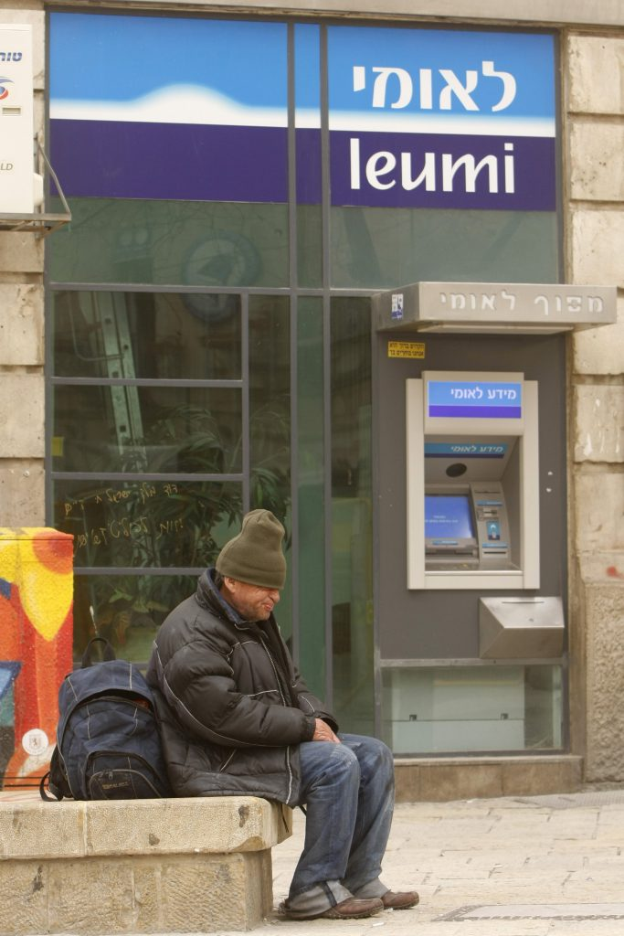 A poor man sits near an ATM of Bank Leumi in Yerushalayim. (Miriam Alster/Flash90)