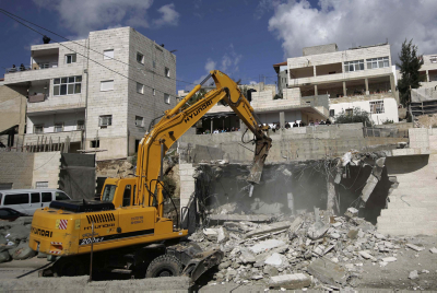 A bulldozer takes apart a house during a destruction of an illegal structure in the village of Isawiyyeh. Photo by Mohamar Awad / FLASH90