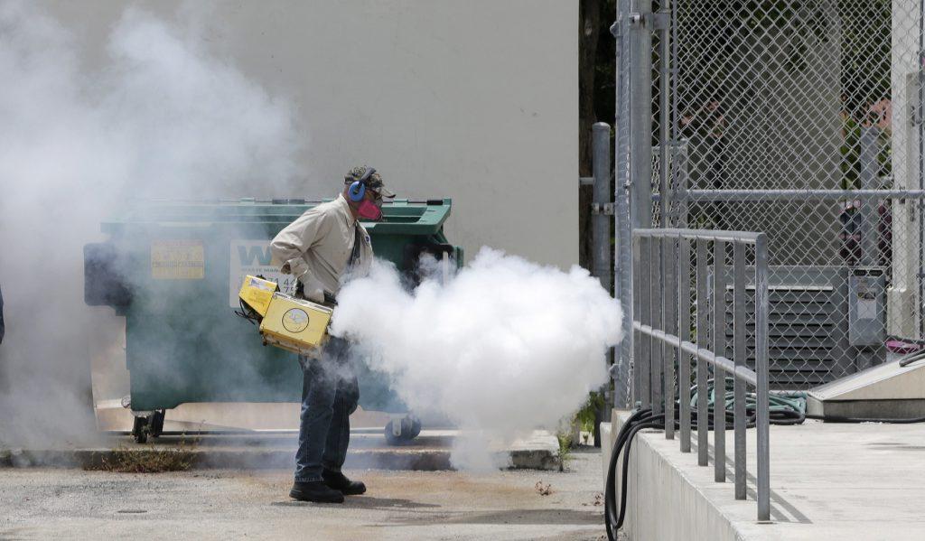 A Miami-Dade County mosquito control worker sprays around a school in the Wynwood area of Miami on Monday. (AP Photo/Alan Diaz)