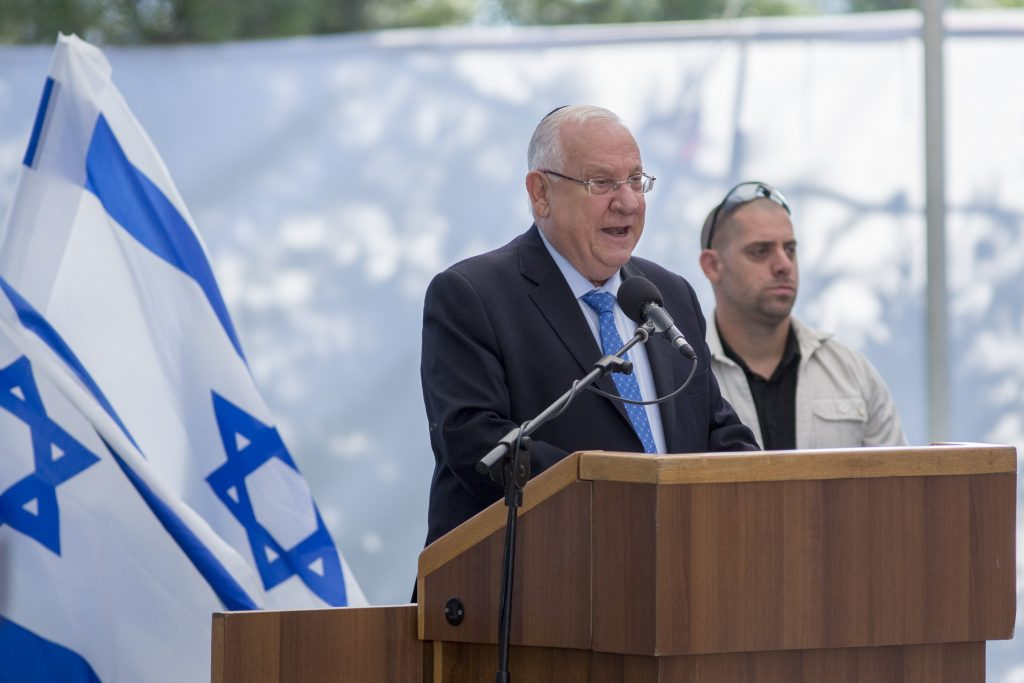 Israeli President Reuven Rivlin, seen here speaking at an event with a flag in the background. A proposed new law would make display of the flag mandatory. (Yonatan Sindel/Flash90)