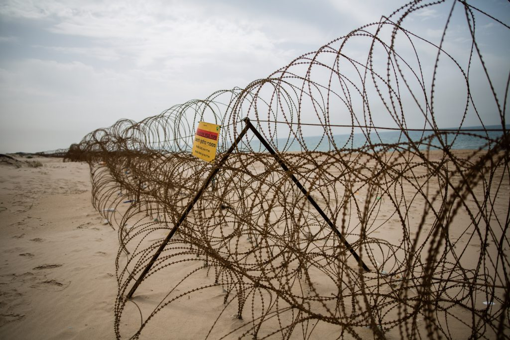 A barbed wire fence on Zikim beach, near the border with the northern Gaza Strip. (Corinna Kern/Flash90)