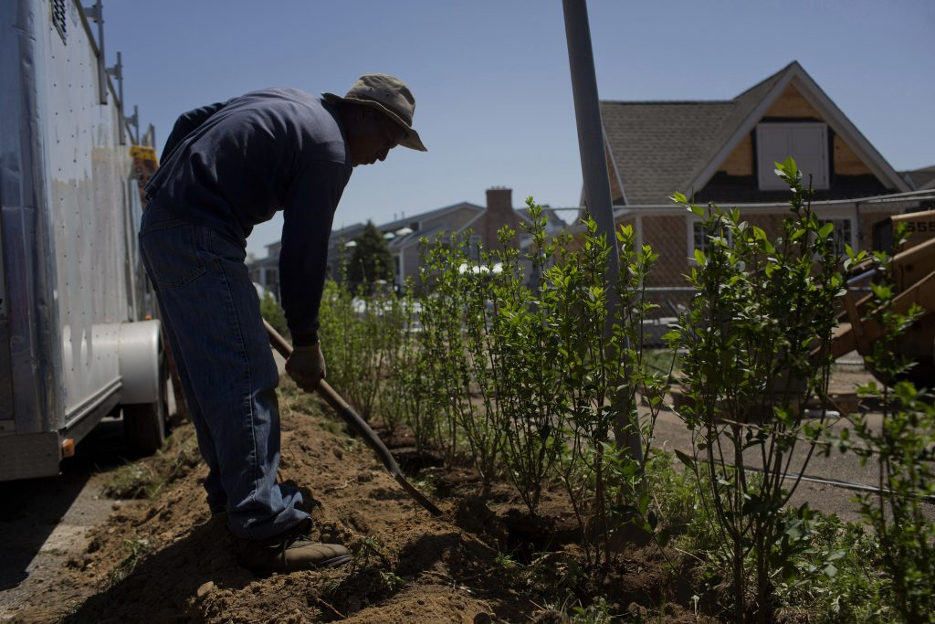 A worker prepares landscaping at a Hamptons hotel and restaurant. (Victor J. Blue/Bloomberg)