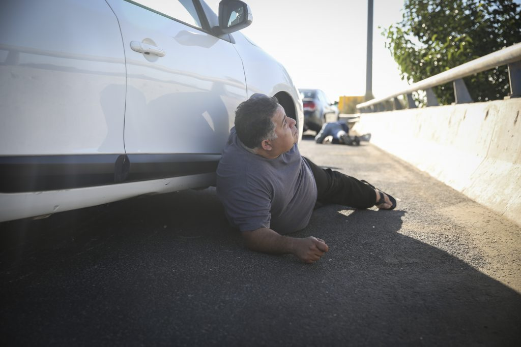 An Israeli man seen taking cover after pulling over on the Yerushalayim-Tel Aviv Route 1, at the sound of the Code Red siren warning of incoming rockets, on July 17, 2014. (Hadas Parush/Flash90)