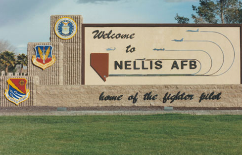 """The United States Air Force Warfare Center, Nellis Base, in Nevada. A welcome sign with a yellow bullseye symbol identifies the base as the """"home of the fighter pilot."""""""